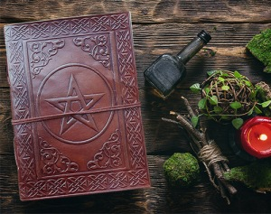 Spell book, magic potion and dryed herbs on the wizard table bac